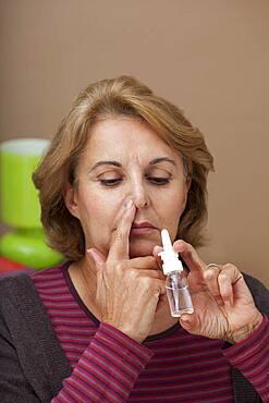 Elderly person using nose spray