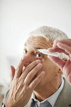 Elderly person using eye lotion