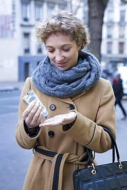 Woman applying cream on her hands.