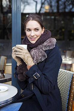Woman drinking coffe at a terrace.