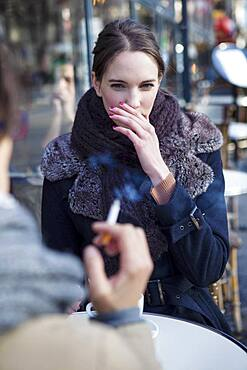 Woman bothered by cigarette smoke.