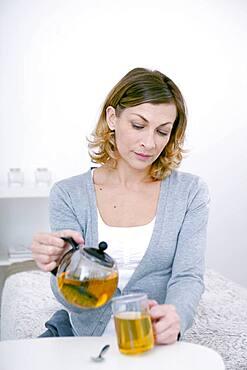 Woman pouring herbal tea.