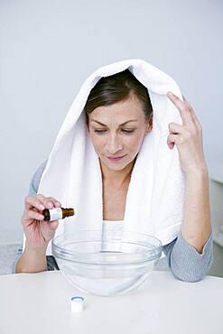 Woman preparing inhalation with essential oil.