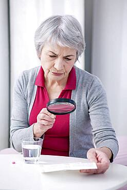 Senior woman reading medication instruction sheet with a magnifying glass.