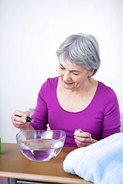 Senior woman preparing inhalation with essential oil.