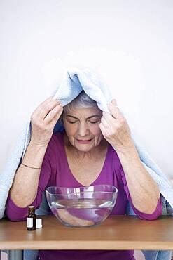 Senior woman doing inhalation.