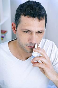 Man using nasal spray.