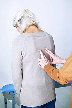 Doctor examining the back of a patient.