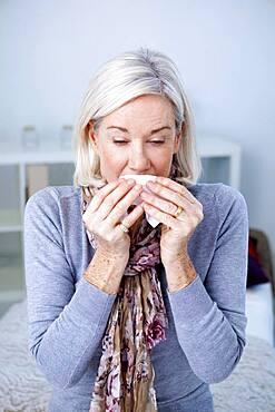 Senior woman sneezing.