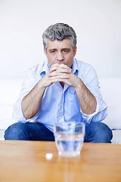 Man hesitating to take a medicine.