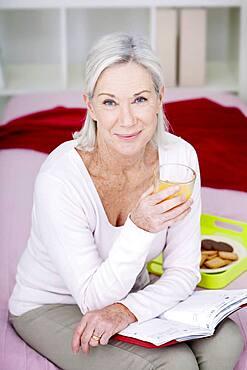 Senior woman drinking orange juice.
