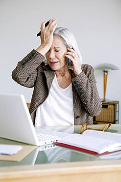 Senior woman working at home.