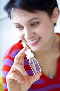 Woman using nose spray