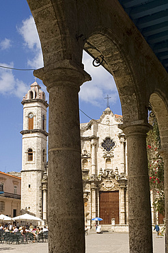 Catedral de San Cristobal and a cafe viewed through the arches of an arcade in the Plaza de la Catedral, Habana Vieja (old town), Havana, Cuba, West Indies, Central America