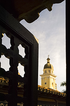 The belltower of Catedral de la Anuncion seen through the wooden screens of Casa de Diego Velazquez, Santiago de Cuba, Cuba, West Indies, Central America