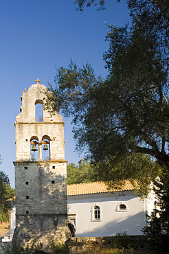 The stone belltower of Agios Constantinos surrounded by olive trees, Paxos, Ionian Islands, Greek Islands, Greece, Europe