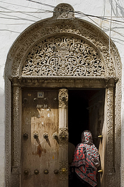 Woman wearing colourful headscarf going through a carved wooden Arab door in Stone Town, Zanzibar, Tanzania, East Africa