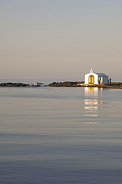 A small white washed church at the end of a quay in the village Yeoryioupolis near Hania on the north coast of Crete, Greece, Europe