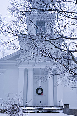 A traditional style wooden church with a Christmas wreath on the front door surrounded by snow, Rensselaerville, New York State, United States of America, North America