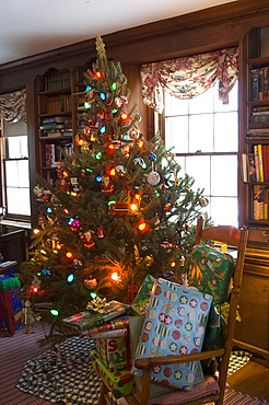 A Christmas tree decorated with lights and ornaments surrounded by gifts on Christmas morning, United States of America, North America