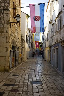 Medieval flags and stone paving in the main shopping street, Srednja Street, Rab Town, island of Rab, Kvarner region, Croatia, Europe