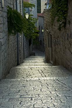 Worn stone steps between high walls in Rab Town, island of Rab, Kvarner region, Croatia, Europe