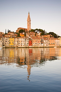 The Cathedral of St. Euphemia and Venetian style buildings in Rovinj reflected in the sea at sunrise, Rovinj, Istria, Croatia, Europe