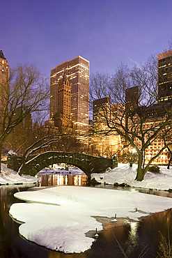 A view of the Gapstow Bridge in Central Park and city skyline at dusk after a snow storm, New York City, New York State, USA