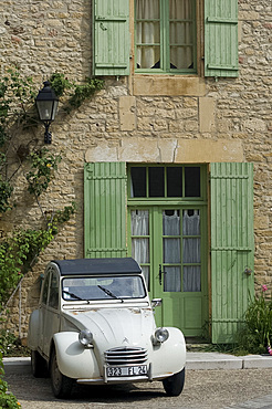 An old Deux Chevaux car parked in front of an old village house, Dordogne, France, Europe