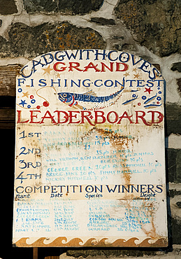 An old painted wooden sign in Cadgwith Harbour on the Lizard Peninsula in Cornwall, England, United Kingdom, Europe