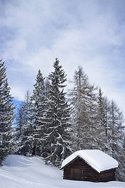 An old wooden barn covered with snow at the Alta Badia ski resort near Corvara in the Dolomites, South Tyrol, Italy, Europe