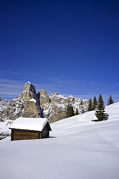 A snow covered wooden barn at the Alta Badia ski resort and Sassongher mountain behind, Corvara, The Dolomites, South Tyrol, Italy, Europe