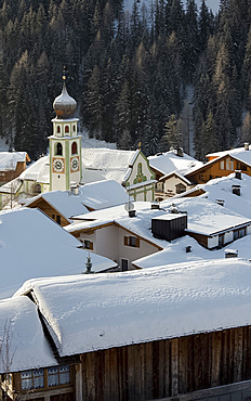 An early morning view of snow covered rooftops in San Cassiano near the Alta Badia ski area, Dolomites, South Tyrol, Italy, Europe