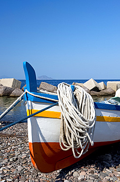 A colourful wooden fishing boat on the rocky beach at Lingua, Salina, The Aeolian Islands, off Sicily, Messina Province, Italy, Mediterranean, Europe