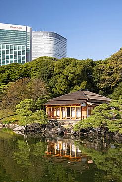 A modern highrise hotel above the Tsubame-no-ochaya, a tea house on a lake in the Hama-rikyu Gardens, Tokyo, Honshu, Japan, Asia