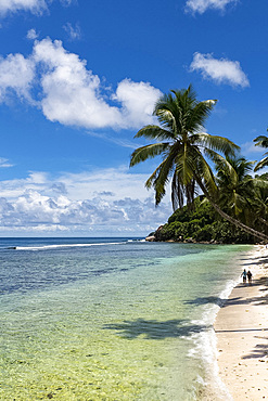 A couple walking along Anse Parnel on the southeast coast of Mahe, Seychelles, Indian Ocean, Africa