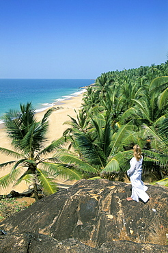 Woman looking over coconut palms to the beach, Kovalam, Kerala state, India, Asia