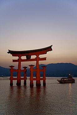 Vermillion coloured 'floating' torii gate (O-torii gate) illuminated at dusk, a Shinto shrine gate, UNESCO World Heritage Site, Itsuku-shima, Miyajima, Hiroshima, Honshu Island, Japan, Asia
