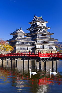 Matsumoto-jo (Matsumoto Castle), the three-turreted donjon built in 1595 in contrasting black and white, surrounded by a moat with access across ornate red bridges, Matsumoto, Nagano Prefecture, Chubu, Central Honshu, Japan, Asia