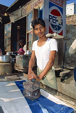 Man ironing pair of jeans, Fatehpur Sikri, Uttar Pradesh, India, Asia