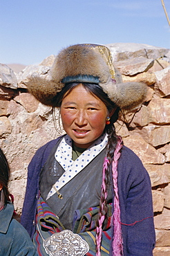 Portrait of a village woman wearing fur trimmed hat, Tibet, China, Asia