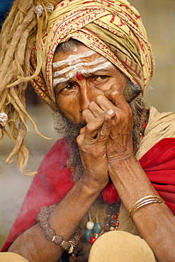Portrait of a Sadhu or holy man smoking a pipe, in Kathmandu, Nepal, Asia