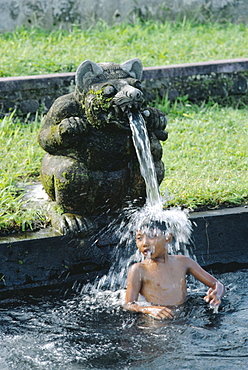 Boy under a water spout, WaterTemple, Bali, Indonesia