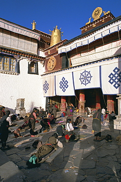 Tibetan Buddhist pilgrims prostrating in front of the Jokhang temple, Lhasa, Tibet, China, Asia