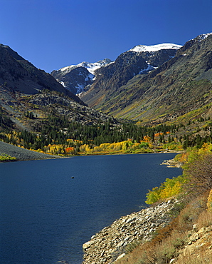 Landscape of June Lake with trees in fall colours and snow capped mountains in the background, in California, United States of America, North America