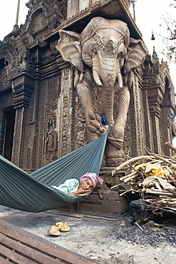 Homeless woman in a hammock attached to an elephant carving in a central temple in Phnom Penh, Cambodia, Indochina, Southeast Asia, Asia