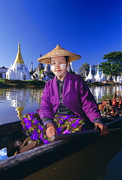 Portrait of a woman in a boat, wearing a straw hat and face paste, Phaung Daw U Kyaung, Inle Lake, Shan State, Myanmar (Burma), Asia