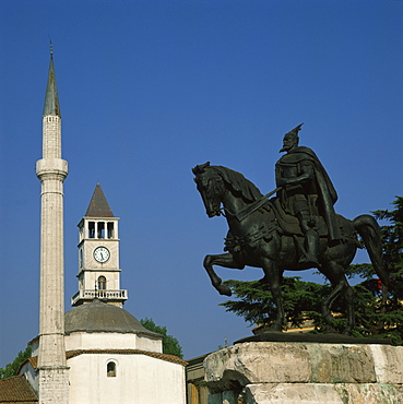 The statue of Skanderberg with the clock tower and minaret of the mosque beyond in Tirana, Albania, Europe