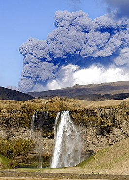 Distant view of the Seljalandsfoss waterfall with the ash plume of the Eyjafjallajokull eruption in the distance, near Hella, southern Iceland, Iceland, Polar Regions