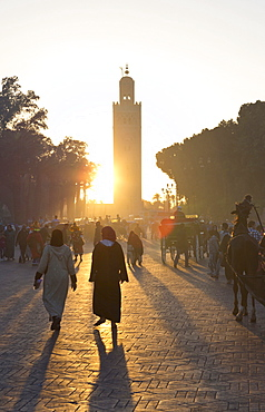 View towards the Koutoubia Minaret at sunset with local people walking through the scene, Djemaa el Fna, Marrakech, Morocco, North Africa, Africa